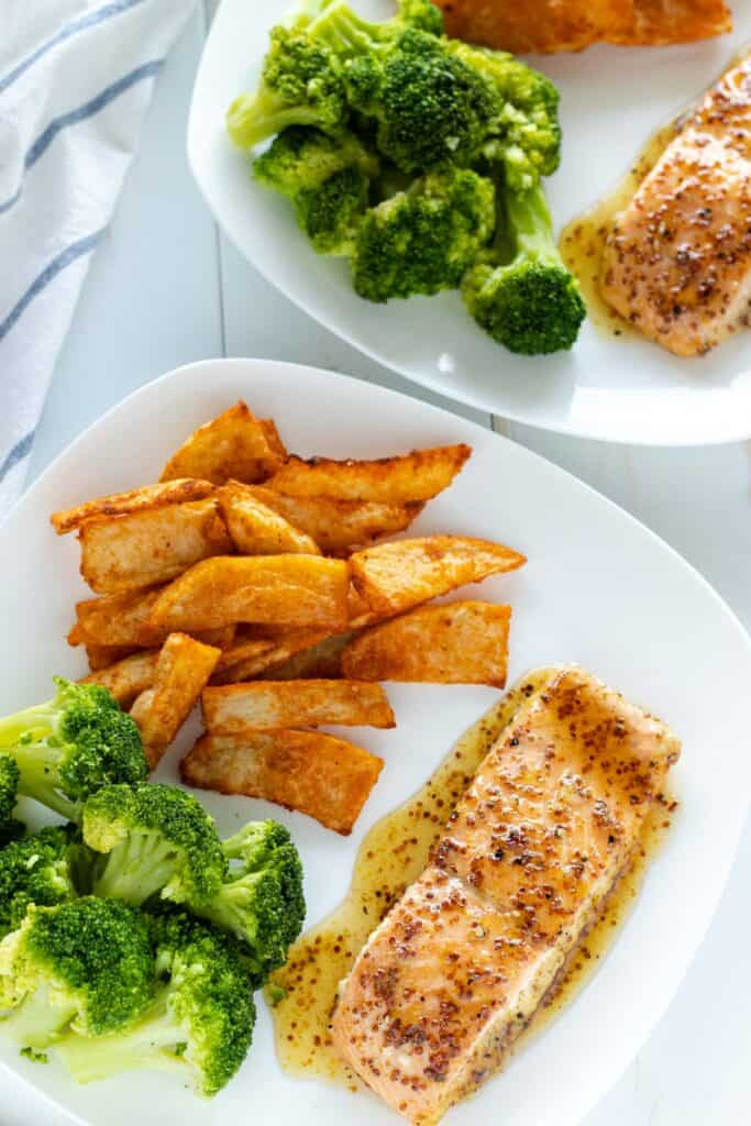 two servings of honey dijon salmon, served with steamed broccoli and seasoned wedge fries