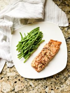 Honey Dijon salmon on a white plate, served with steamed green beans