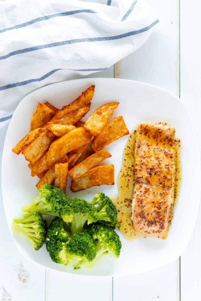 a well rounded meal of salmon, wedge fries, and steamed broccoli