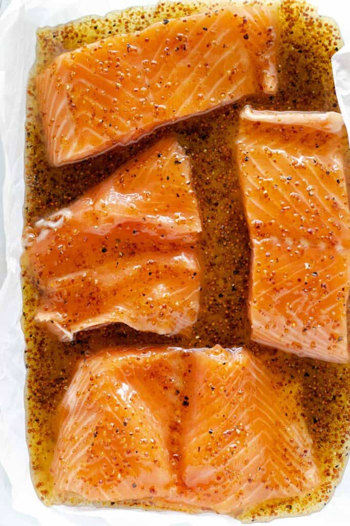 pouring the honey dijon sauce on top of salmon fillets in a parchment lined baking dish