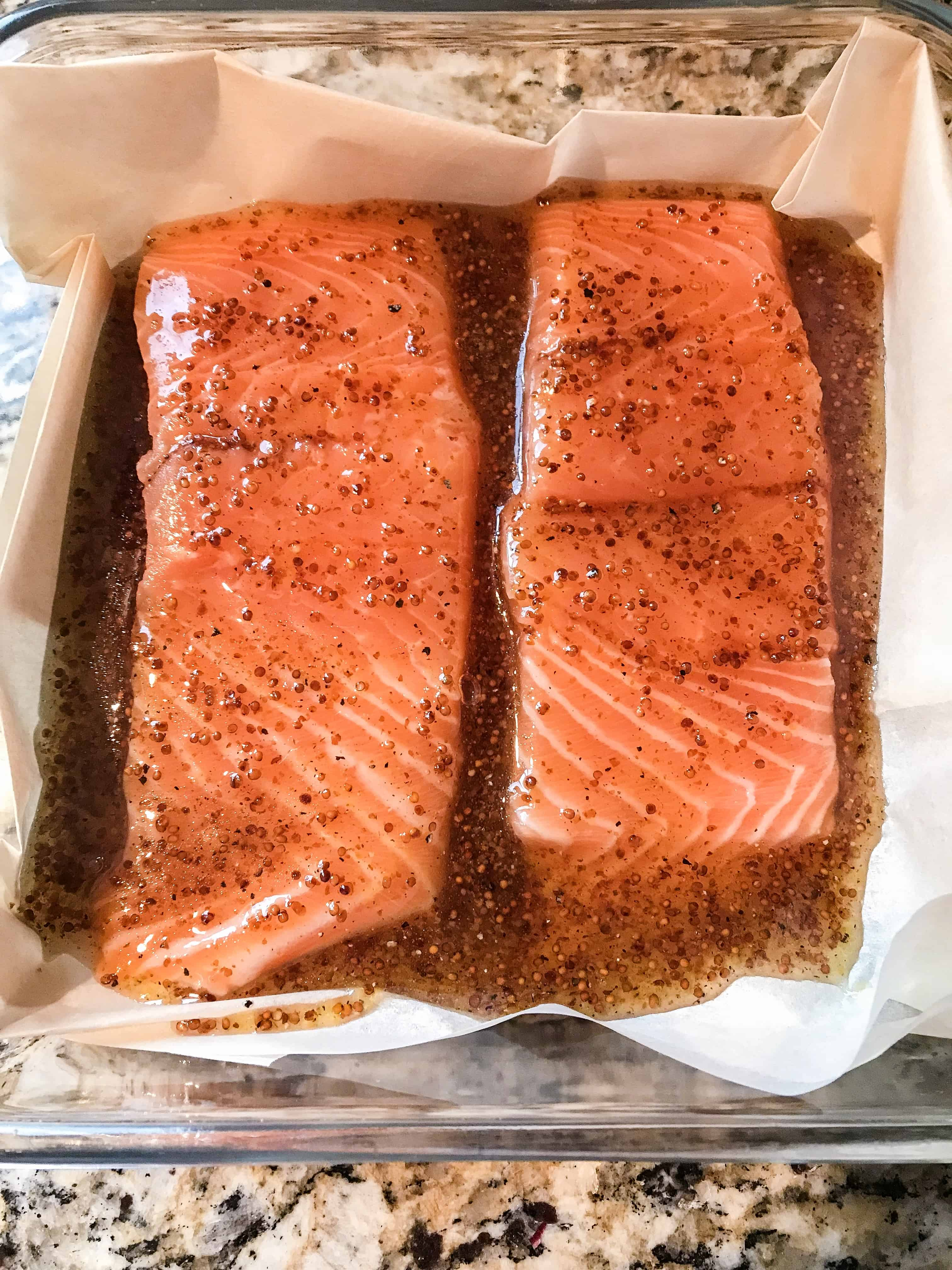 Uncooked honey dijon salmon in a baking dish, smothered in the honey dijon sauce