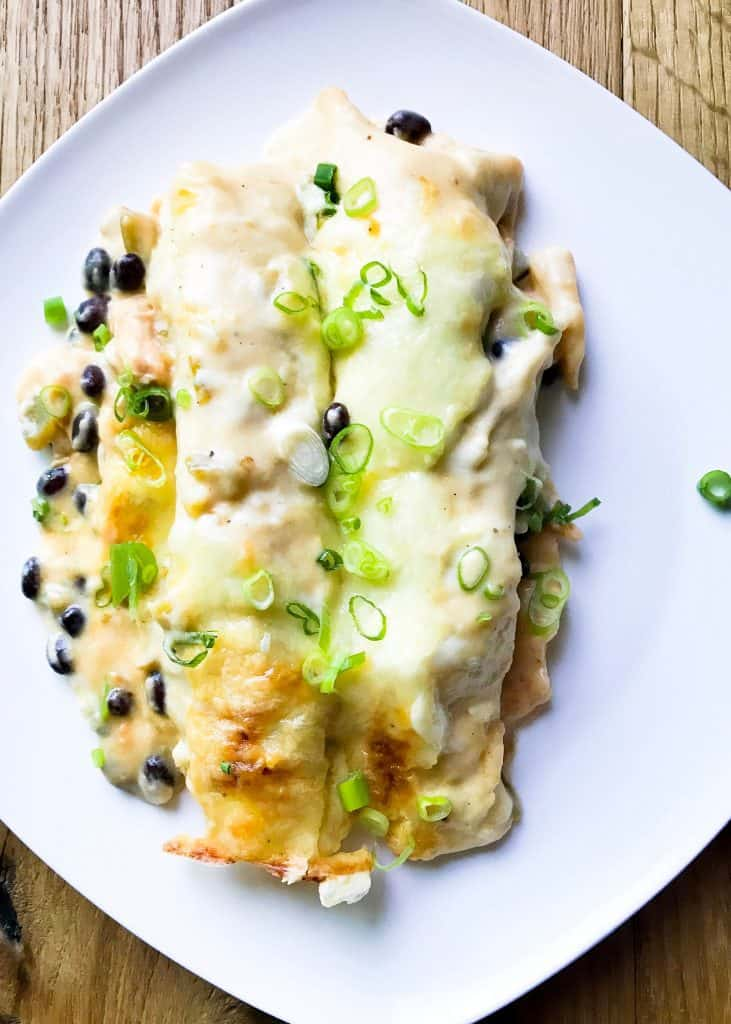 Spicy Black Bean Chicken Enchiladas on a white plate with thinly sliced scallions sprinkled on top