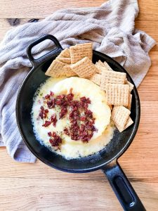 Baked brie melted in a cast iron pan with crackers on the side