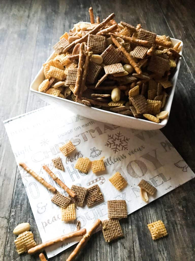 Sweet & Spicy Holiday Chex in a square bowl, with some spilled out over the side. Holiday napkin for decoration