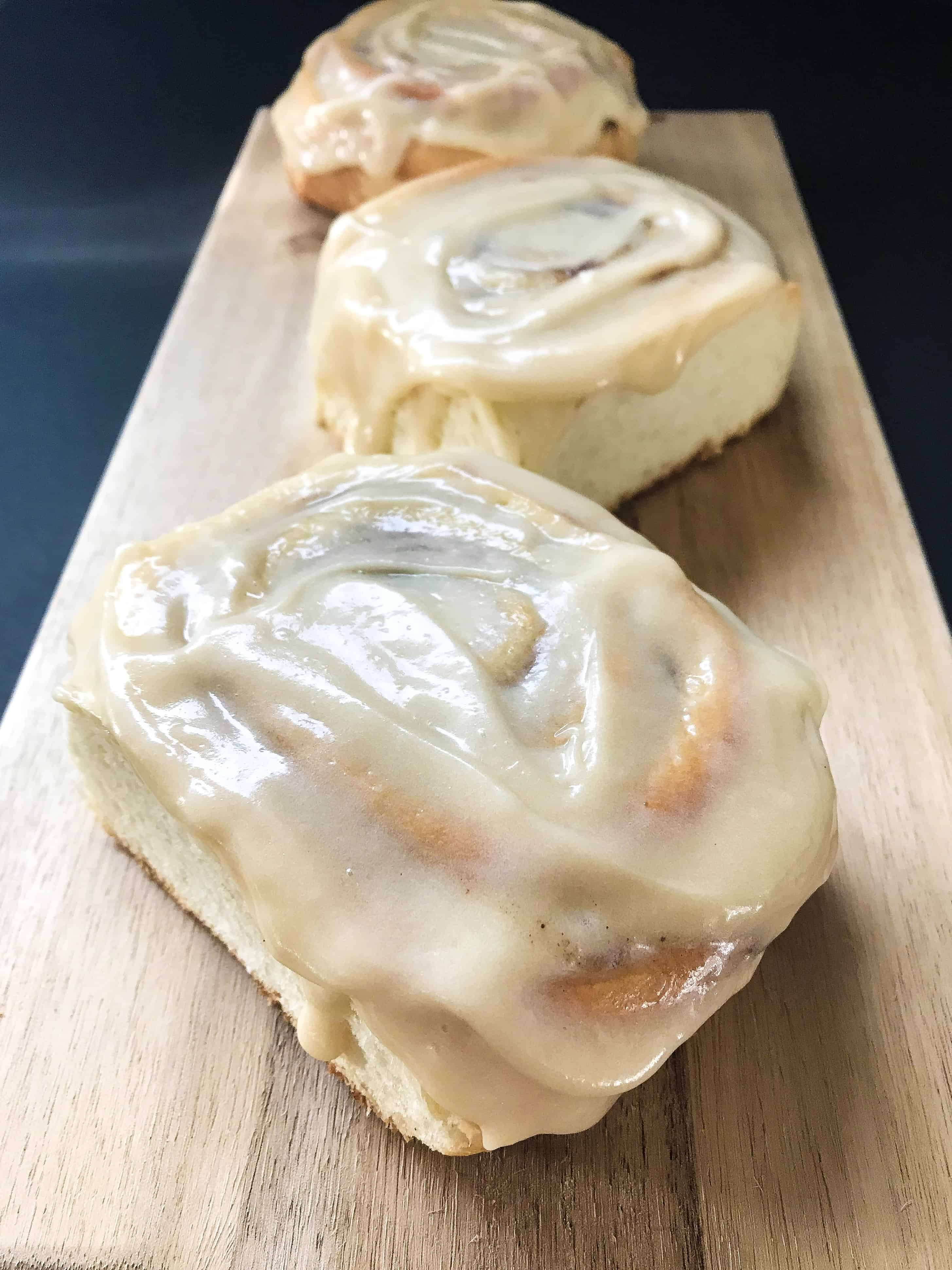 3 homemade cinnamon buns on a wooden tray, a side photograph, showing the cream cheese frosting dripping down the sides