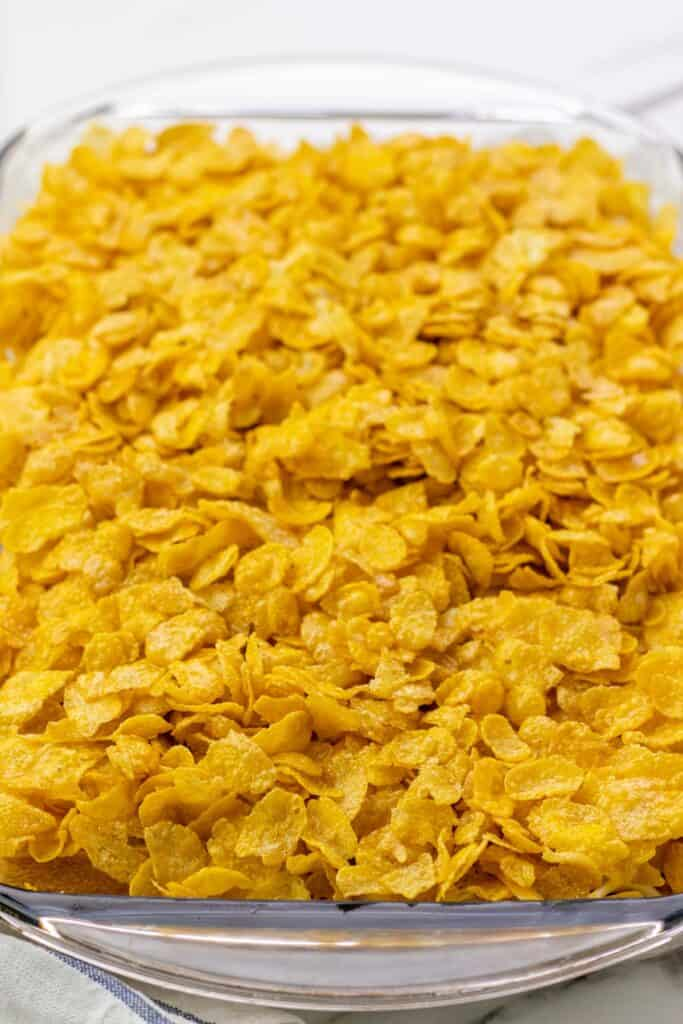 spreading the corn flake topping on top of the casserole
