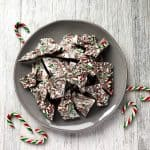 Peppermint candy cane bark on a grey plate, with whole candy canes sprinkled around the plate as decoration