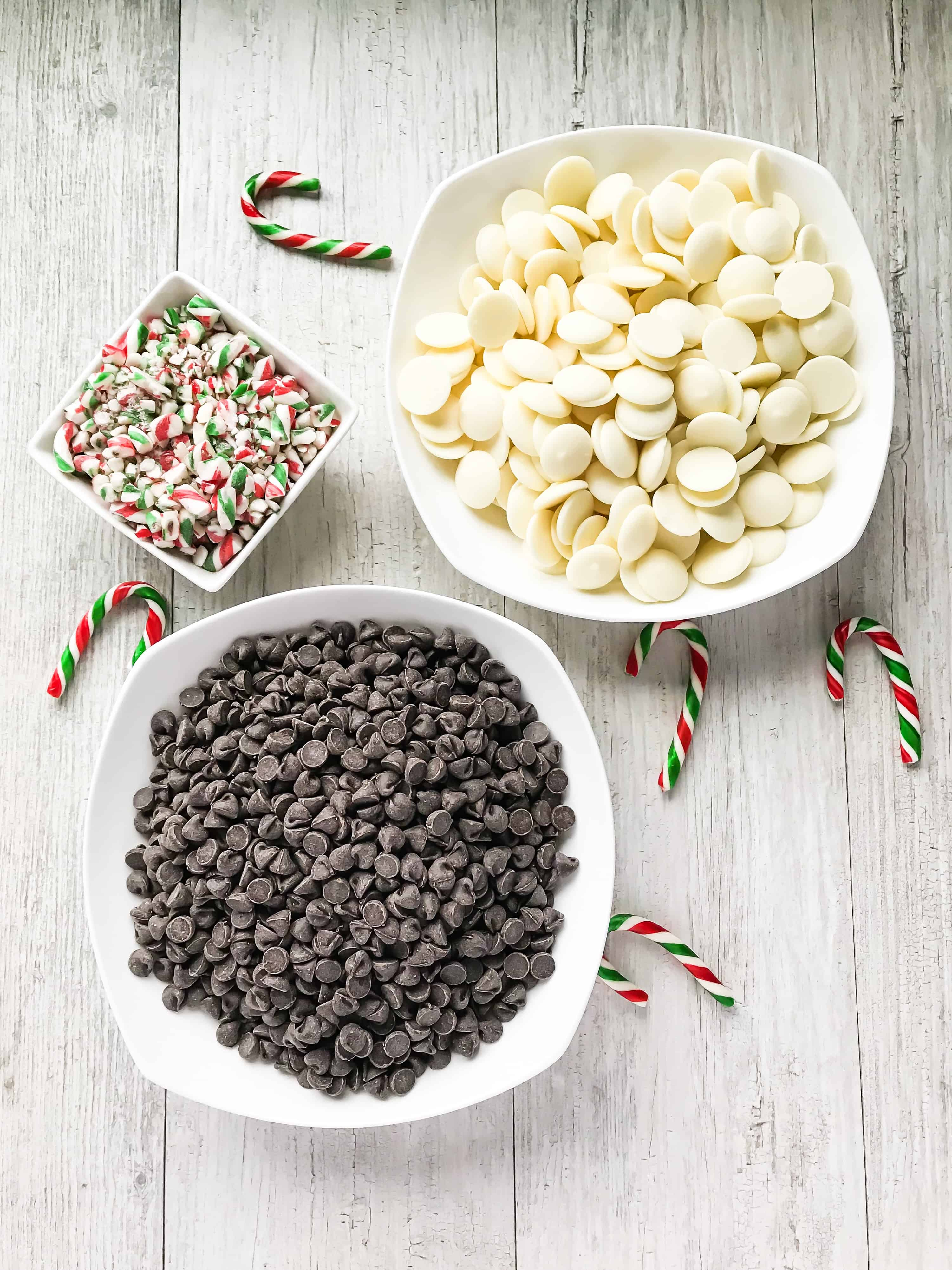 Peppermint candy cane bark preparation with white, semi sweet, and crushed candy canes in white bowls