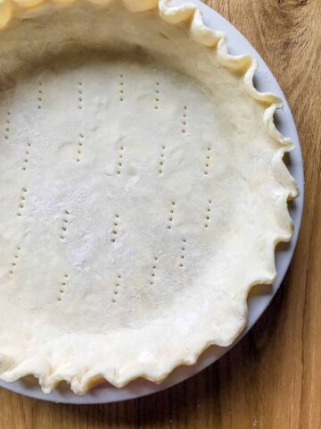 assembled pie crust with a fluted edge in a white pie dish