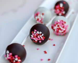 five cake pops on a white plate side view, only the middle is in focus, with heart sprinkles