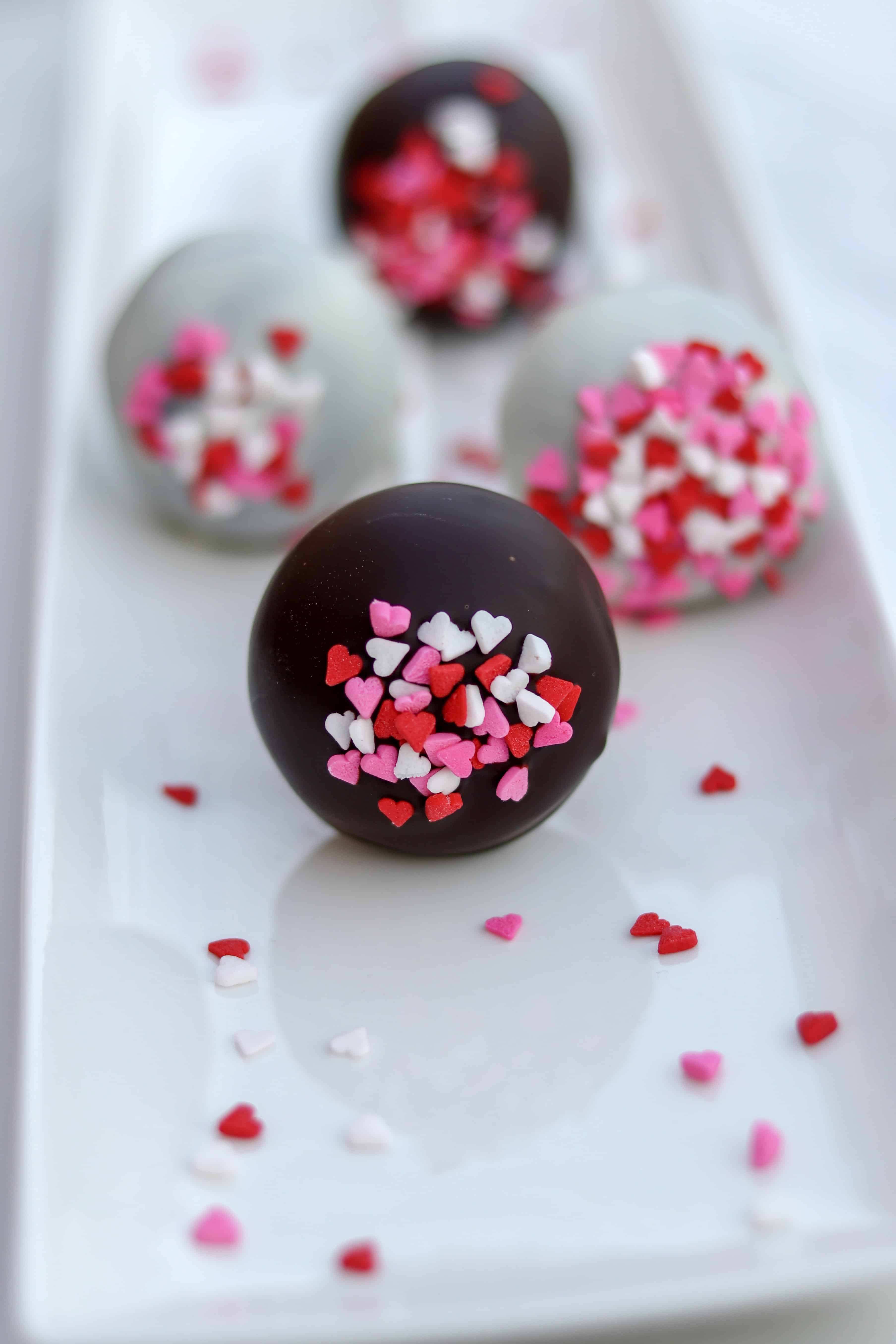 four cake pops on a white plate straight on view, back 3 are blurred out with the front in perfect focus