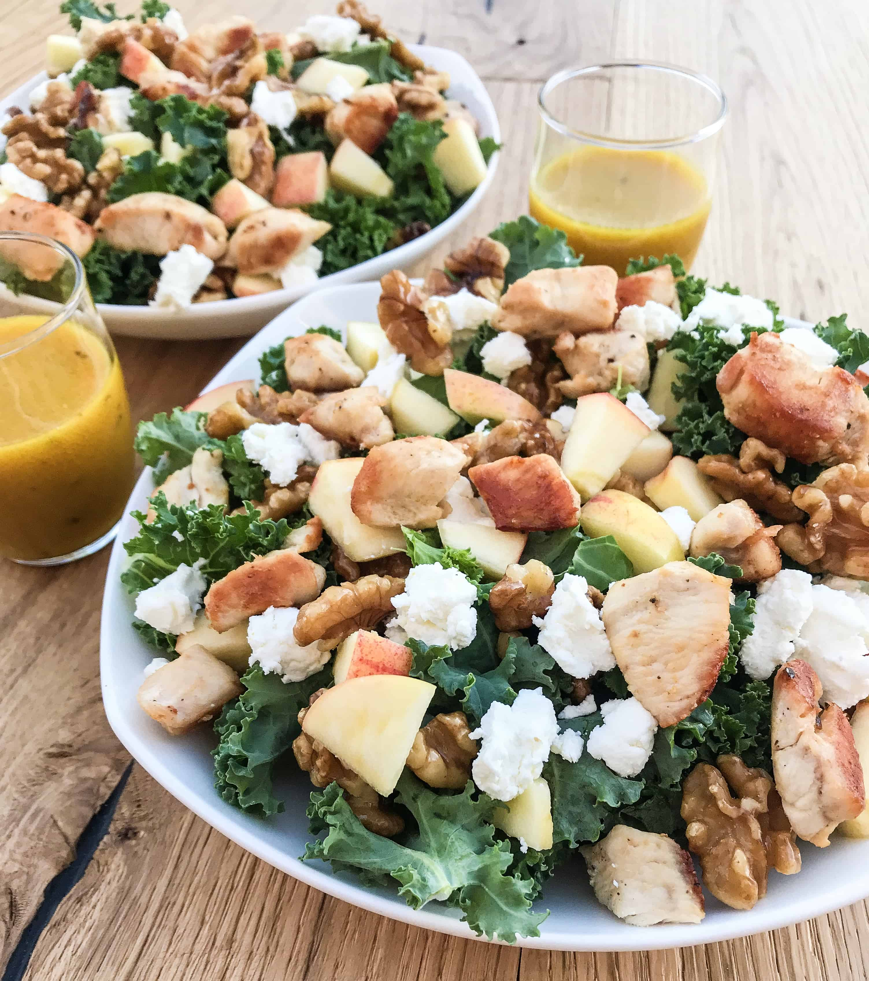 close up of kale apple salad with crumbled goat cheese, maple candied walnuts, apple, chicken, and honey mustard vinaigrette on the side