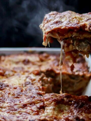 Baked lasagna, one piece being lifted out by a spatula, melted cheese dripping down, surrounded by a cloud of steam