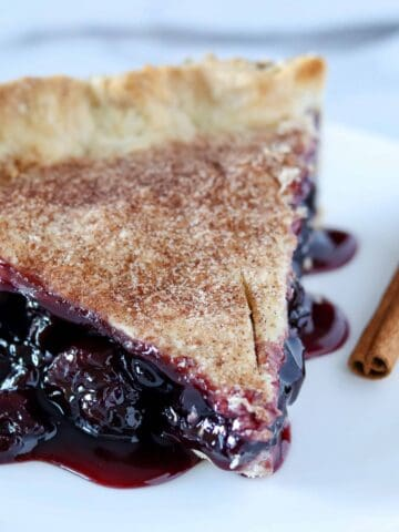 slice of cherry rum pie with a cinnamon stick on the side as garnish