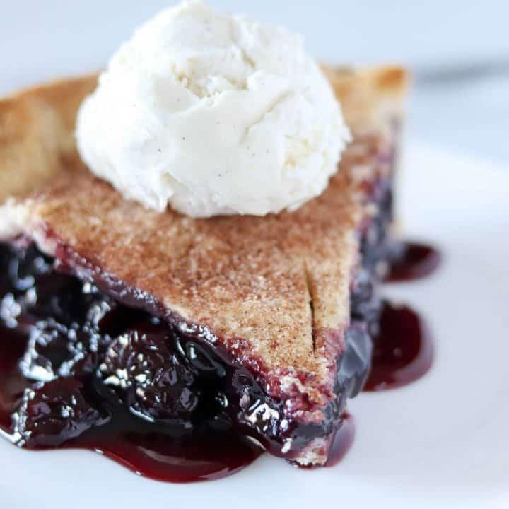 slice of cherry rum pie with vanilla bean ice cream on top