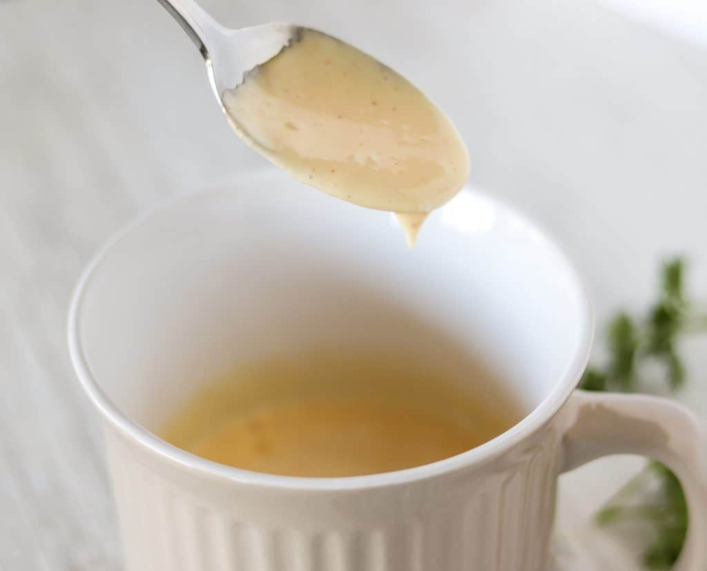 hollandaise sauce being scooped out of ramekin with a spoon