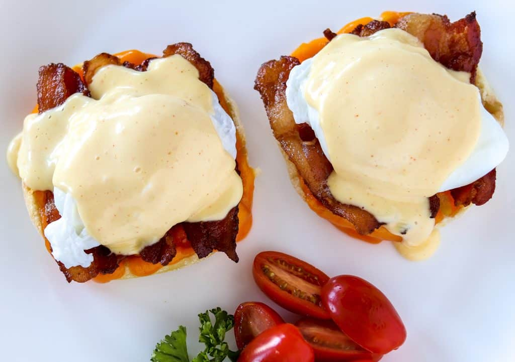 classic eggs Benedict on a white plate with hollandaise sauce dripping down the side and tomatoes on the side
