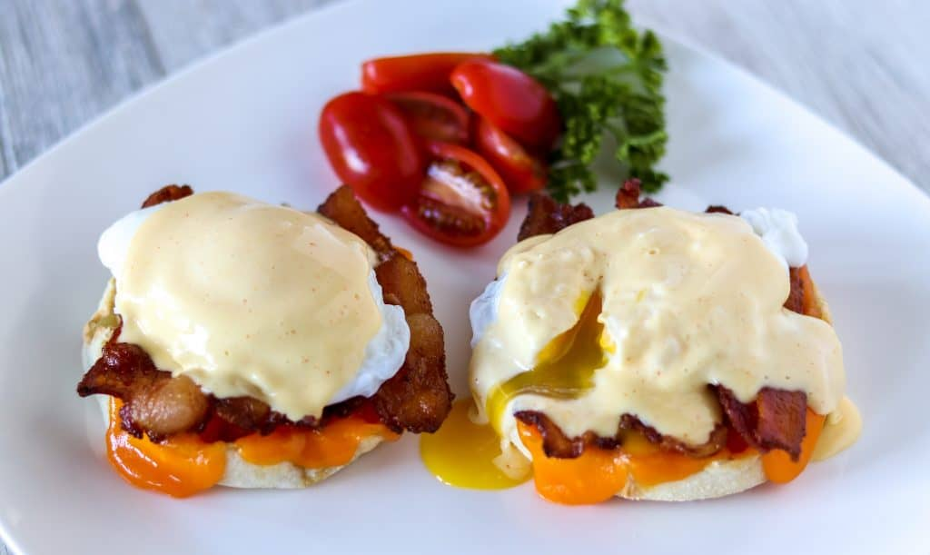 sliced open classic eggs Benedict on a white plate with hollandaise sauce and egg yolk dripping down the side and tomatoes on the side