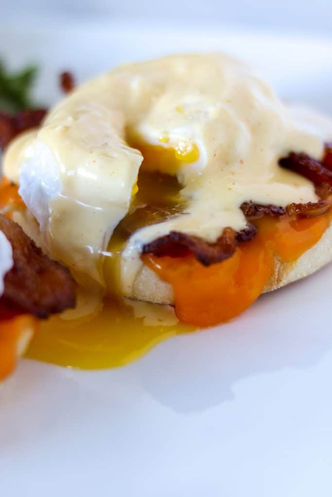 Close up of a sliced open classic eggs Benedict on a white plate with hollandaise sauce and egg yolk dripping down the side