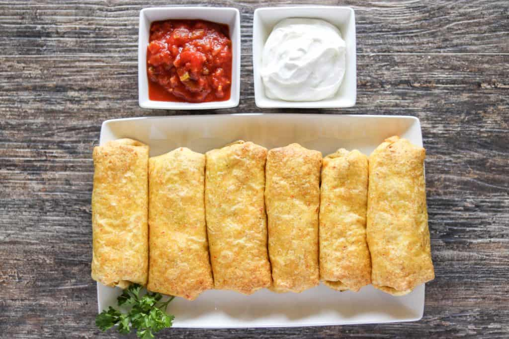 Baked Chicken and Cheese Chimichangas lined up on a serving plate with sour cream and salsa on the side