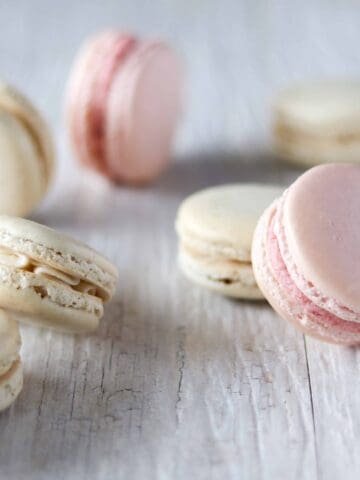 scattered strawberry and french vanilla french macarons on a white background