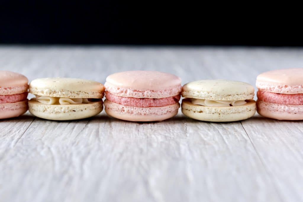 strawberry and french macarons all in a horizontal line across the screen