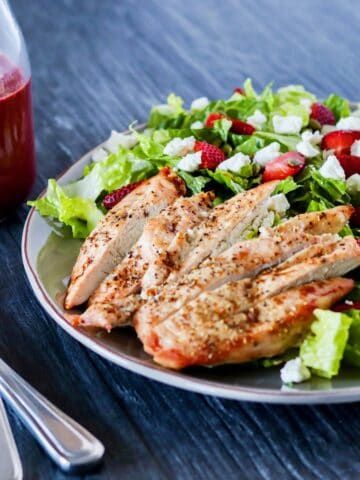 strawberry goat cheese chicken salad with berry vinaigrette on a grey plate, with a fork and knife, and a bottle of berry vinaigrette in the background