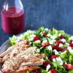strawberry goat cheese chicken salad with berry vinaigrette on a grey plate, and a bottle of berry vinaigrette in the background