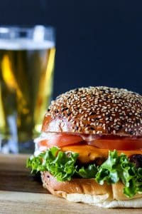 a blackened chicken sandwich on a wooden serving board with a beer in the background