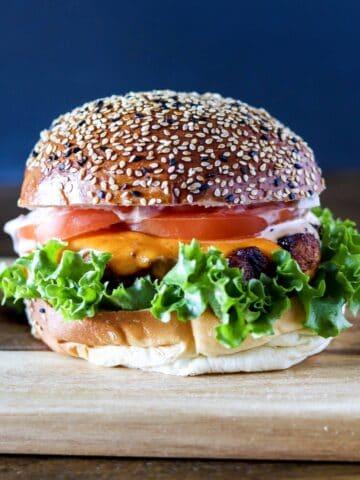 a blackened chicken sandwich on a wooden serving board