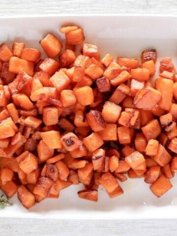 Pan Fried Maple Sweet Potatoes on a white serving plate with fresh sprigs of thyme in the corner