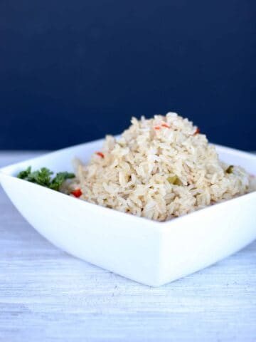 Brown rice with peppers piled high in a white serving bowl