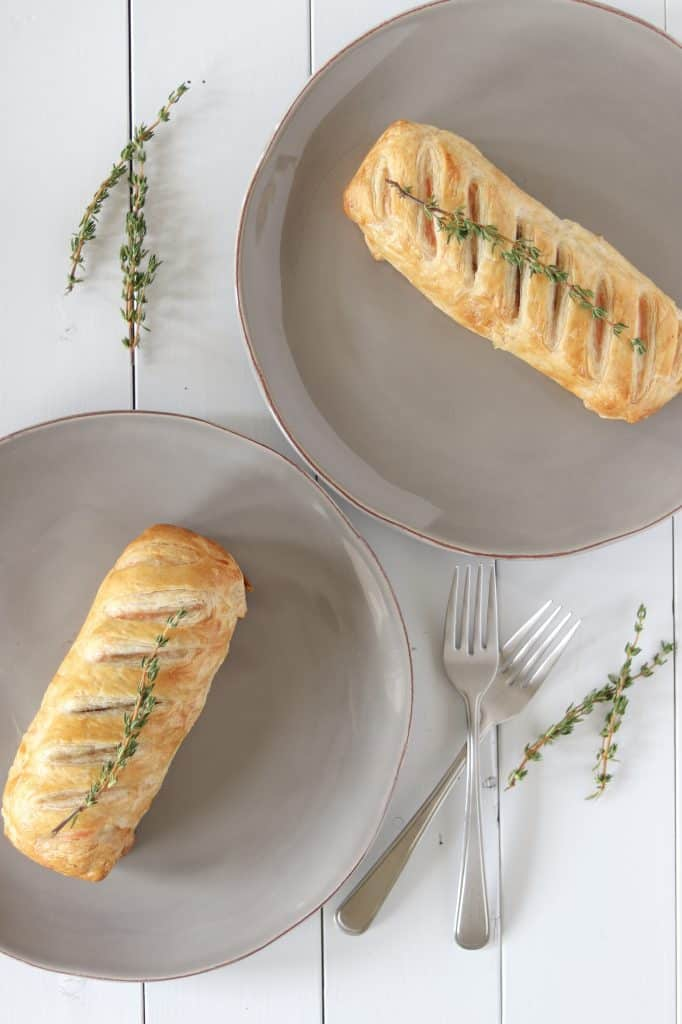 over head picture of salmon wellington cooked on a grey plate and garnished with fresh thyme