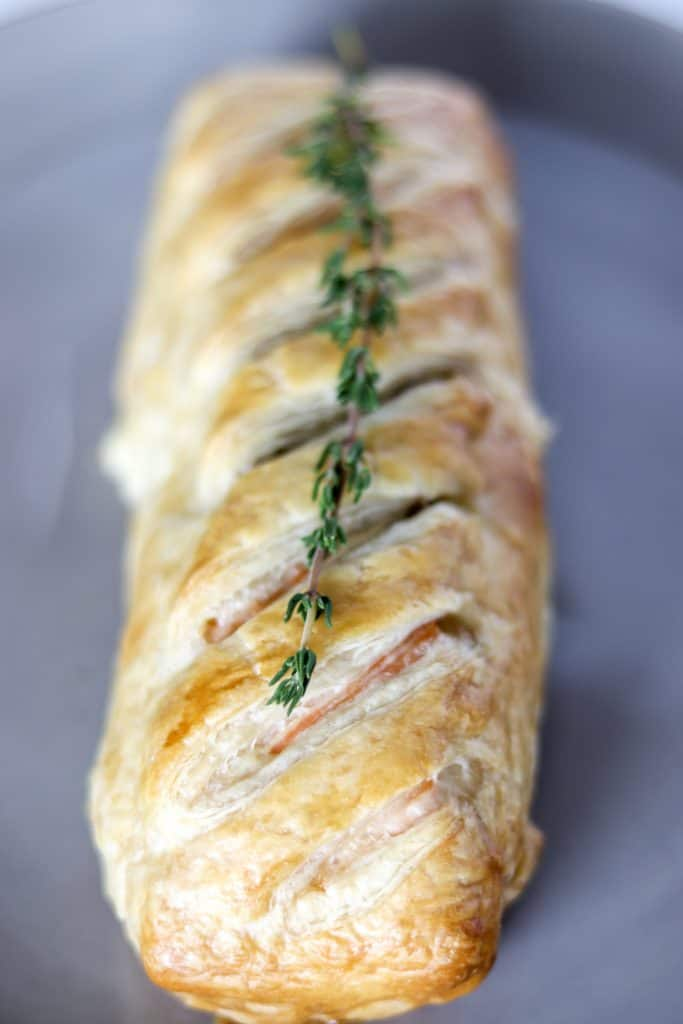 head on picture of salmon wellington cooked on a grey plate and garnished with fresh thyme
