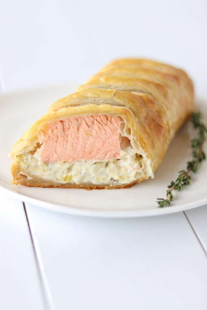 Close up of a piece of salmon wellington sliced open showing the cooked salmon and artichoke layers