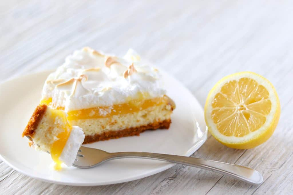 Slice of lemon meringue cheesecake on a white plate with a fork full of cheesecake with a half a lemon as garnish