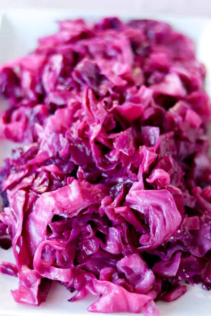 side angle picture of sauteed red cabbage on a white serving plate