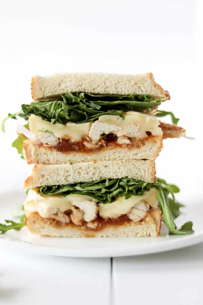Aprict brie chicken sandwich stacked with arugula sprinkled around the background