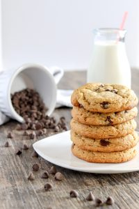 a stack of peanut butter banana chocolate chip cookies on a white plate with a spilled bowl of chocolate chips and a jar of milk in the background