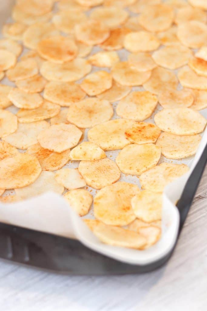 chipotle potato chips spread in a single layer on a baking sheet before they are baked