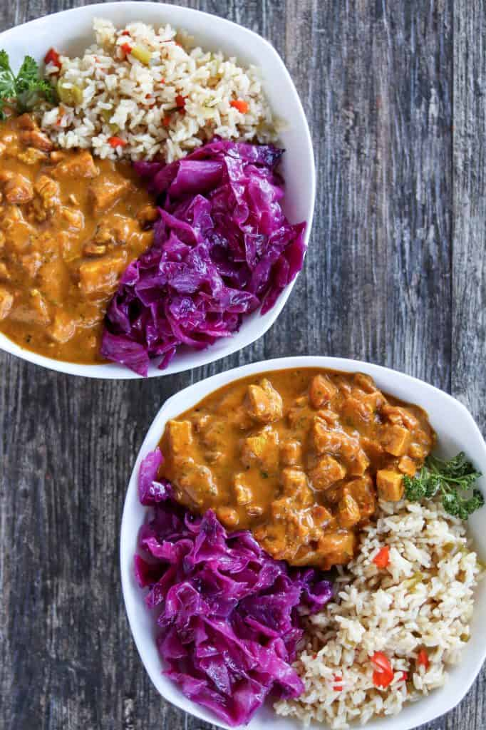 Two bowls of turmeric coconut curry chicken served with sauteed red cabbage and instant pot brown rice & peppers .