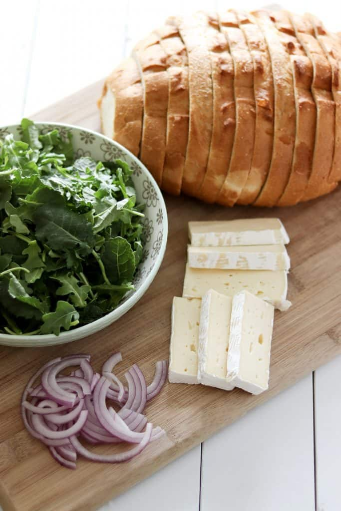 arugula, sourdough, red onion, and brie cheese on a cutting board