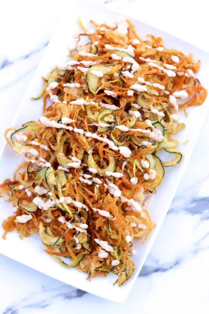 veggie curly fries on a white plate with chipotle drizzled on top