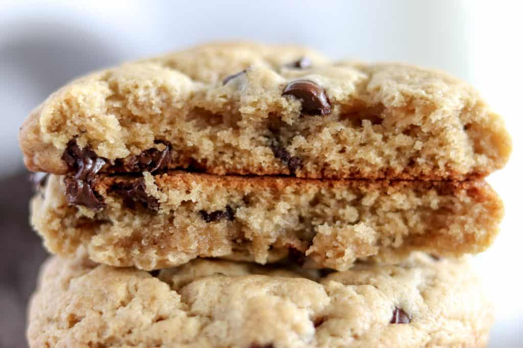 a peanut butter chocolate chip cookie broken in half, filled with gooey chocolate chips