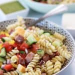 pasta salad in two bowls with basil pesto and caeser salad dressing on the side