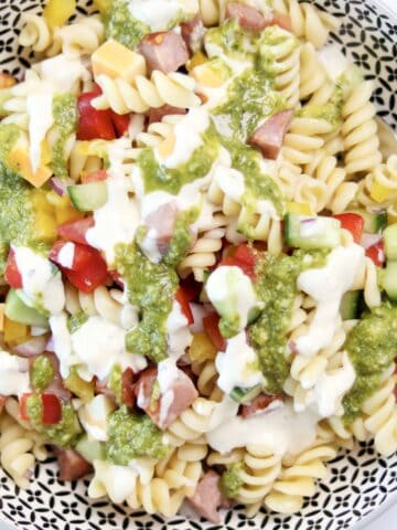 easy pasta salad with basil pesto and caesar dressing drizzled on top