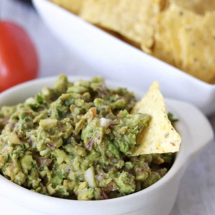 bowl of guacamole with tortilla chips in the background