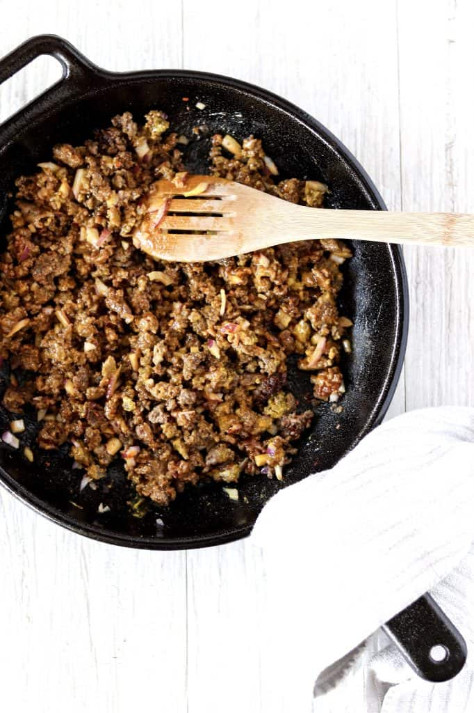 all of the hamburger filling ingredients mixed in a cast iron pan