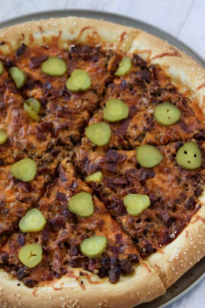 cheeseburger pizza baked, sliced, and topped with pickles