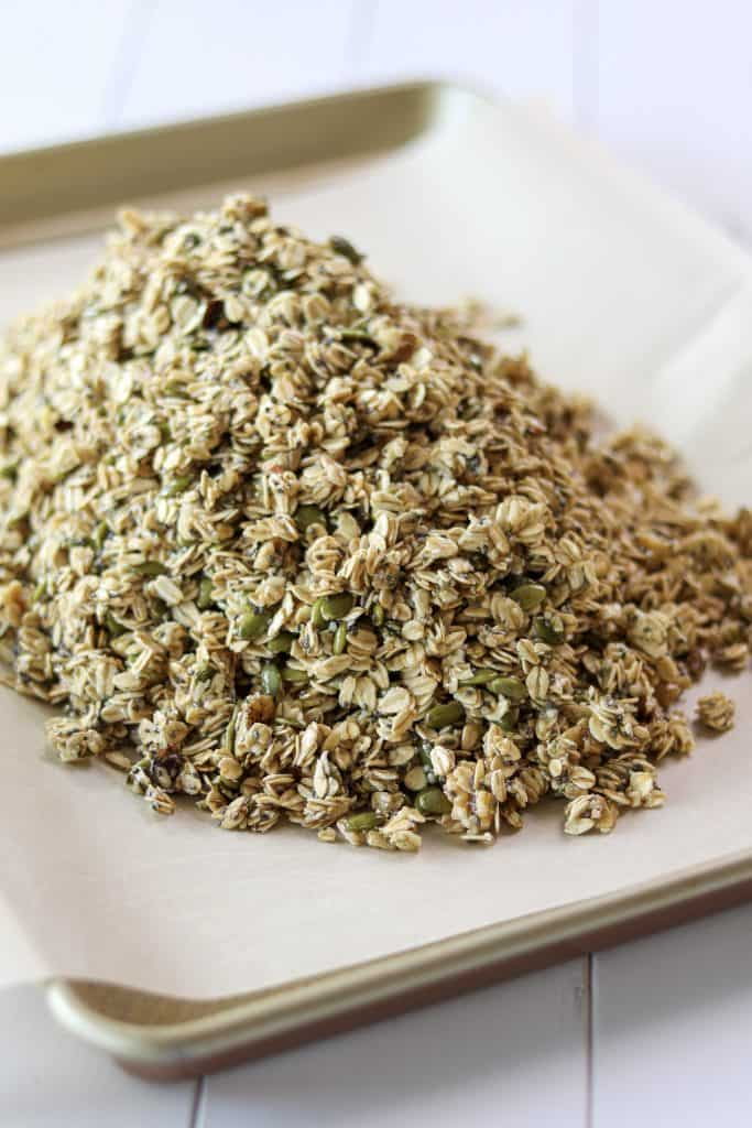 pile of granola mixture on a sheet pan before being spread out into a thin layer